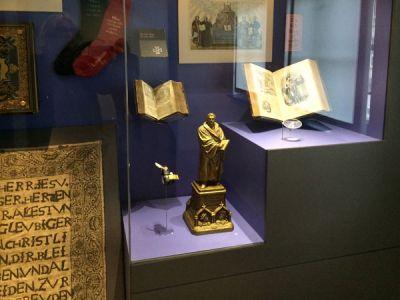 Erinnerungen als Luther in Büsten <br>und Bibeln hinter Glas, darunter der Playmobil-Luther (links unten) <br>und die kleineste Bibel (Mitte rechts vorn)